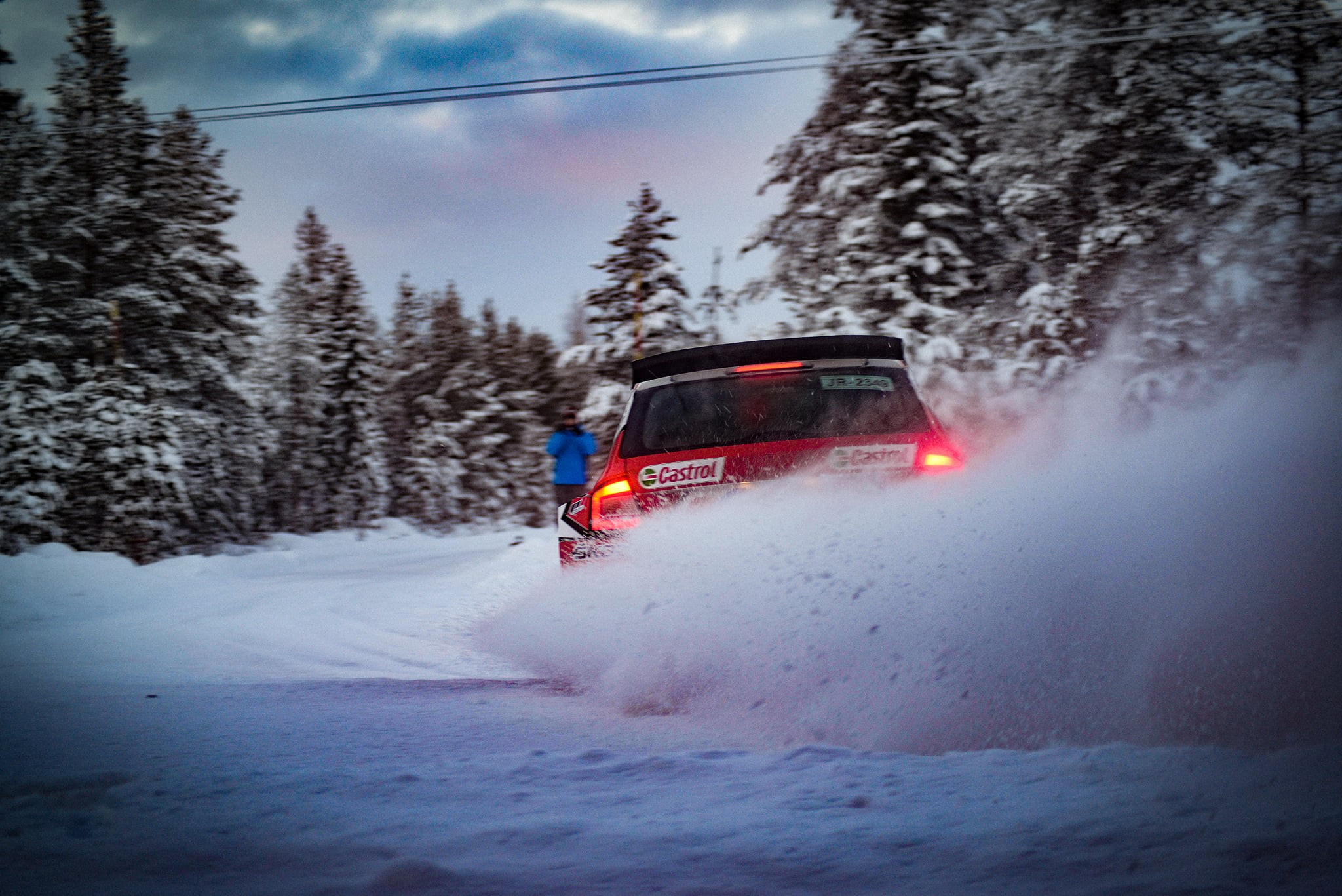 Red Rally car blowing snow as it races away